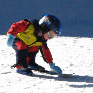 Lucas at age 3, cleaning off his skis at Vail skiing school - there was snow on them !
